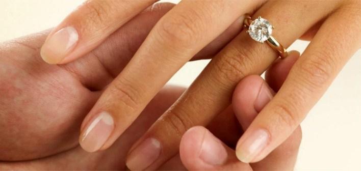 Золотое обручальное кольцо на пальце